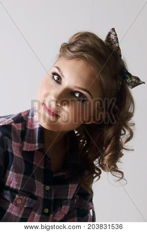 Pinup beautiful young woman in checkered shirt in grey studio