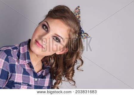 Pinup beautiful young woman in checkered shirt and with curly hair in grey studio