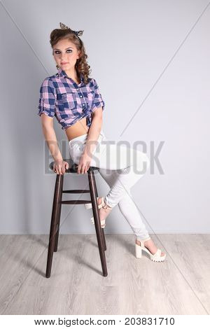 Pinup beautiful woman in checkered shirt on stool in studio