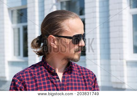 Side looking portrait of cheerful bearded hipster man in black glasses. Fashion stylish young men