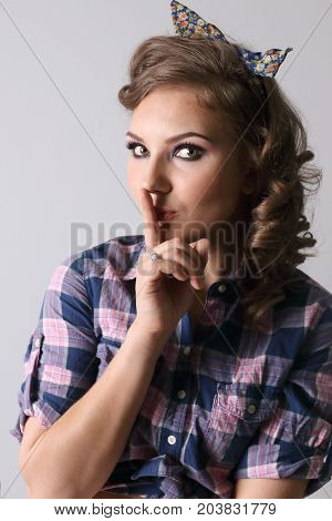 Pinup beautiful woman in checkered shirt shows hist gesture in studio