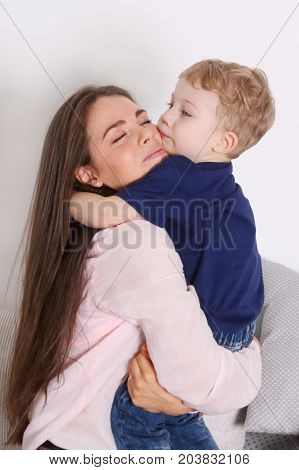 Young mother with long hair embraces her little blonde cute son in room