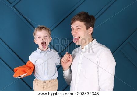 Young handsome father and little son put out tongues in blue studio focus on boy