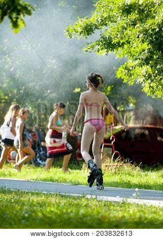 Girl In Bikini Swimwear Drives Roller Skate. Back View