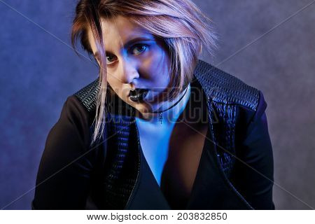 Young girl with black lips and choker in black poses in studio with blue light