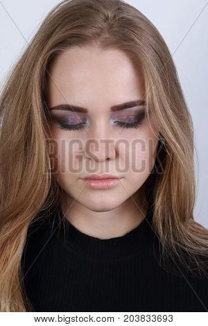 Young blonde in black poses with closed eyes in white studio close up