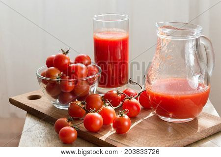 Ripe cherry tomatoes and fresh tomato juice stand on the kitchen table