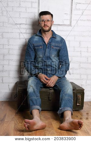 Barefoot man in glasses and denim overalls sits on wooden box in white room