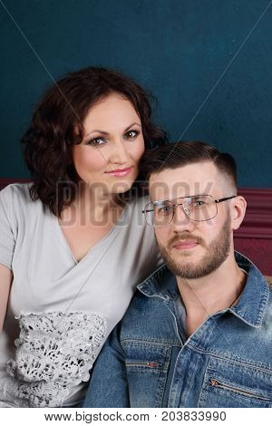 Happy young woman and man in denim overalls pose together in studio