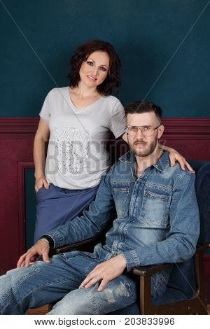 Happy young woman and man in denim overalls pose in studio man sits and woman stands
