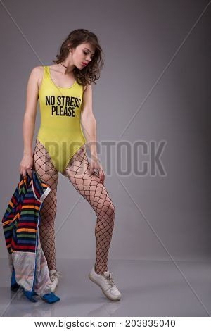Young woman dressing in black pantyhose mesh and yellow swimsuit with inscription No Stress Please staying over gray background and holding a striped jacket in the hands.