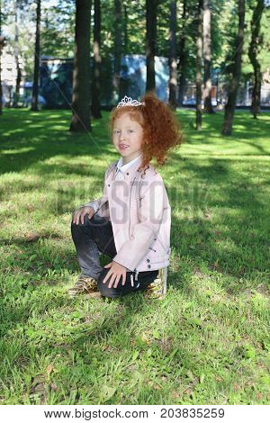 Happy little girl with red hair in diadem in summer green park at sunny day