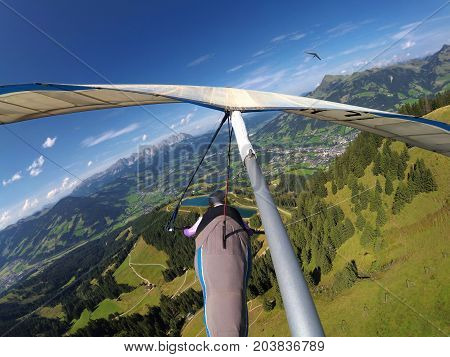 Two hangglider pilots flying over famous Kitzbuhel ski resort in summer.