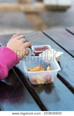 Little girl eating french fries with ketchup and mayonnaise