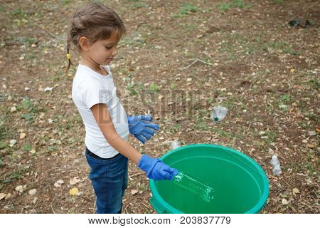Beautiful girl with one green recycle bin on earthen background with different rubbish and dry yellow leaves. Uncultivated outside terrain. Helping child. Concept of envirometal protection.