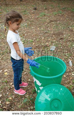 Cute girl on white t-short and blue jeans with one green recycle bin on earthen background with different rubbish and dry yellow leaves. Uncultivated outside terrain. Concept of envirometal protection.