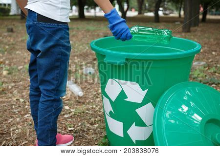 Beautiful girl with one green recycle bin on earthen background with different rubbish and dry yellow leaves. Throwing plastic bag into recycling bin. Helping child. Concept of envirometal protection.