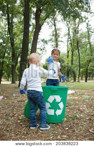 Young boy and pretty girl putting rubbish in the one green recycle bin, which are on earthen background. Enviromental protection concept. Uncleaned outside territory. Helping children in the park.