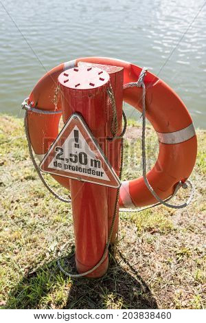 Life buoy or rescue buoy floating near river to rescue people from drowning man. Safety equipment.