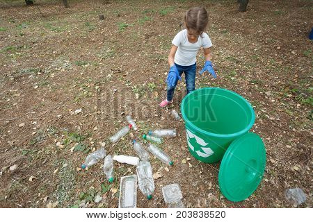 Horizontal photo of small girl with bright recycle bin on earthen background with different rubbish and dry yellow leaves. Uncultivated outside terrain. Helping. Concept of envirometal protection.