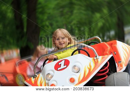 happy cute little girl on roller coaster ride in amusement park