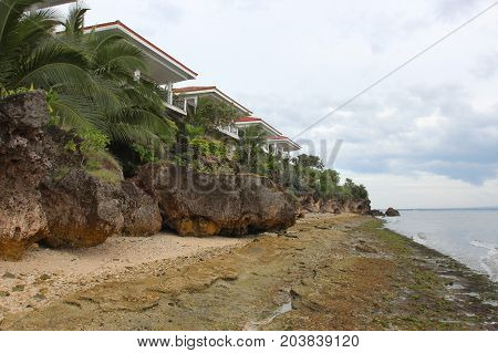 Sandy Beach, Tropical Trees And White Houses With Red Tiles On The Roof
