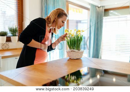 Pregnant woman taking care of flowers in modern kitchen
