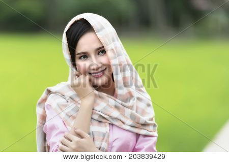 Close up face of beautiful Lao woman wearing local tradition on green rice field background