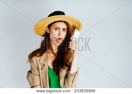Young beautiful girl in a straw hat shows a tongue, offended looks at the camera, holds a phone in hands