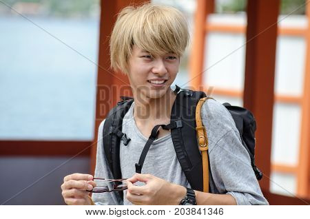 Japanese Blond Colored Tourist Guy Walk On Miyajima (itsukushima) Island.  Japan