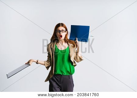 A young woman teacher wearing glasses is surprised, holds a folder of documents, opened her mouth in surprise, looks into the camera
