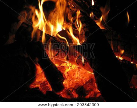 Macro image of flames with coals on a dark black background