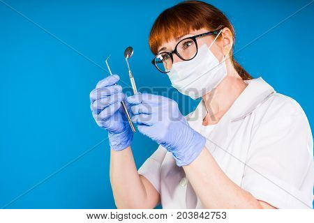 A female dentist with glasses checks the instruments. Isolated on a blue background