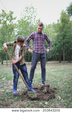 Two boys are planting plants. Two brothers a dig earth in a park for planting a young tree. Image of brothers farmers digging in the garden. Prepare for the planting.