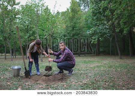 Boy helping his brother to plant the tree in the garden as save world concept, child is going to plant a tree, love and protect nature concept. Two brothers was planting a young tree at the forest.