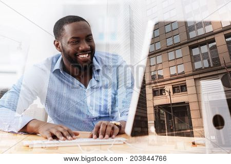 Cheerful mood. Close up of smiling handsome African American working with computer while sitting against city background