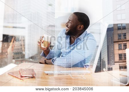 Time for break. Close up of smart handsome worker drinking coffee while looking away and being in a cheerful mood
