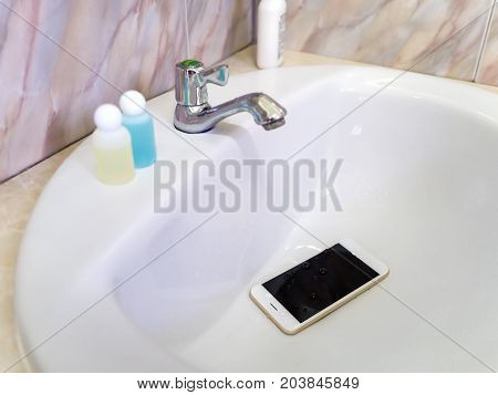 White smart phone droped in wash basin. Water damage waterproof concept.