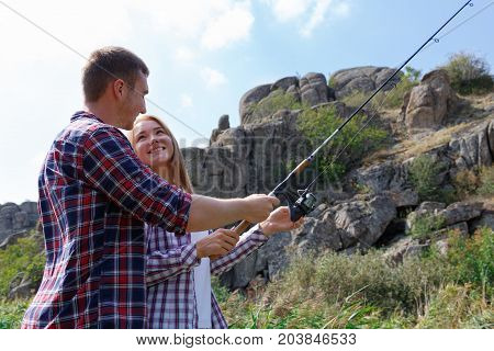 Two young people are fishing in the river for dinner. Romantic fishing for a young couple on the river. A wonderful summer day for fishing with your soul mate. The best pastime in the summer.