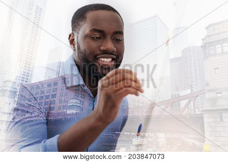 Involved in work. Close up of African American using a pen and writing on the board while being attentive