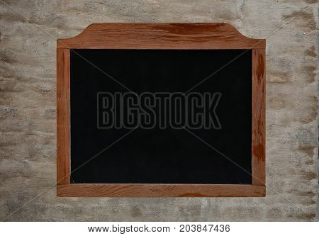 Old black school chalkboard blackboard sign in vintage brown wooden frame over background of grunge uneven gray daub plaster wall close up