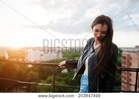 Portrait Of An Attractive Young Woman In Black Leather Jacket, Jeans And Sneakers Standing By The Ha