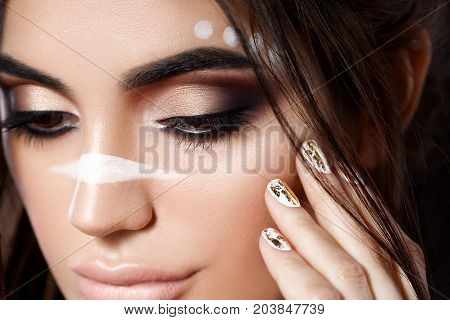 Close up view of beautiful woman touching her face. Perfect skin and evening makeup. Macro studio shot. Sensuality, passion, cosmetology, lip care, plastic surgery or injection concept. Isolated