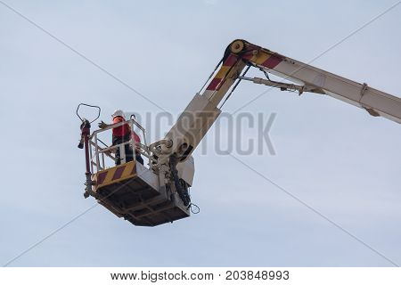 Fireman in a lifting basket against the sky