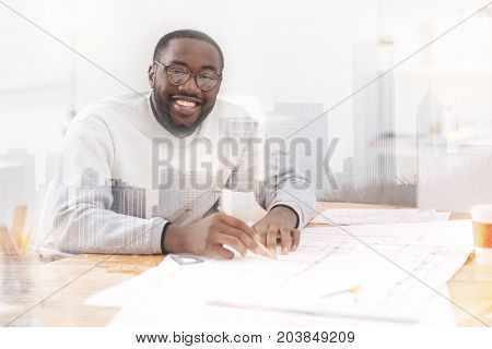 Attention to work. Close up of young bright engineer busy with his sketches while sitting at the table and being showing interest