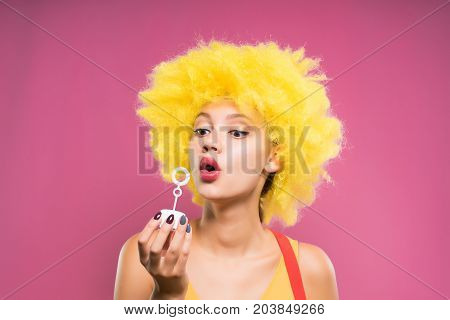 A clown girl in a yellow wig is throwing soap bubbles. Isolated on a pink background