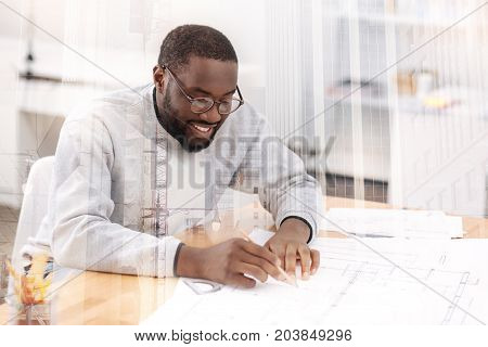 Perfect job. Close up of young attentive engineer sitting at the table and using a pencil while drawing hid new work