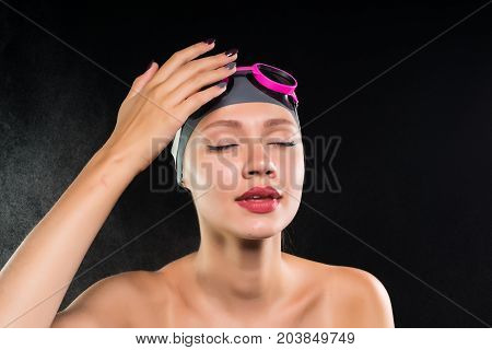 A young girl swimming in a swimming cap and glasses with pleasure closed her eyes