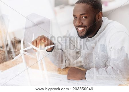 My work. Close up of clever young African American sitting at the table and touching a small windmill while smiling at you
