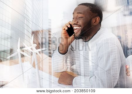 Exciting news. Close up of young amused man talking on the mobile phone while sitting at the table expressing astonishment